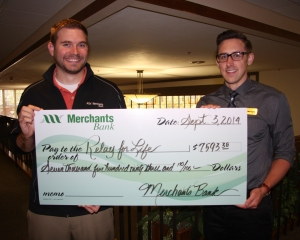 Merchants Bank employees Marcus Krings and Ryan Meyer, two members of the Merchants Relay for Life committee, present the Relay for Life check.
